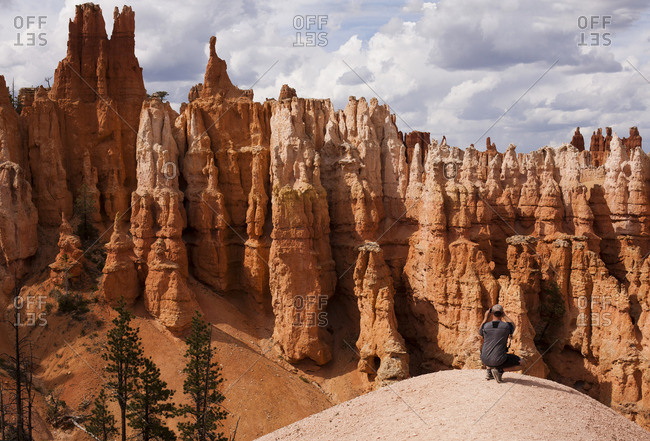 Man photographing hoodoos while crouching on rock