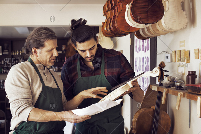 Workers comparing violin with plan while standing in workshop