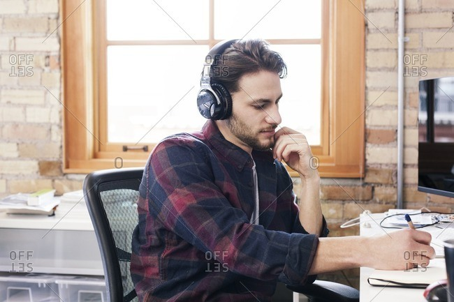 Businessman wearing headphones writing on diary while working in office