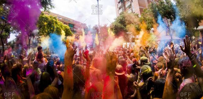 People celebrating Holi festival on city street