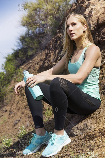 Woman with bottle looking away while sitting on dirt