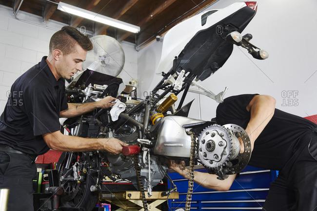 Workers making motorcycle in workshop