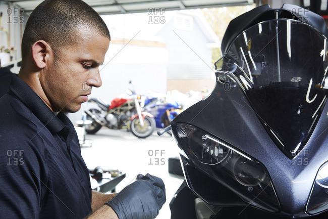 Confident worker working on motorbike in workshop