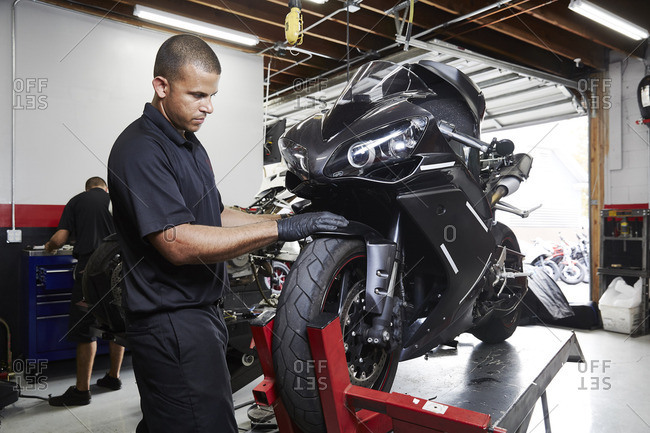 Colleagues making motorcycle in factory