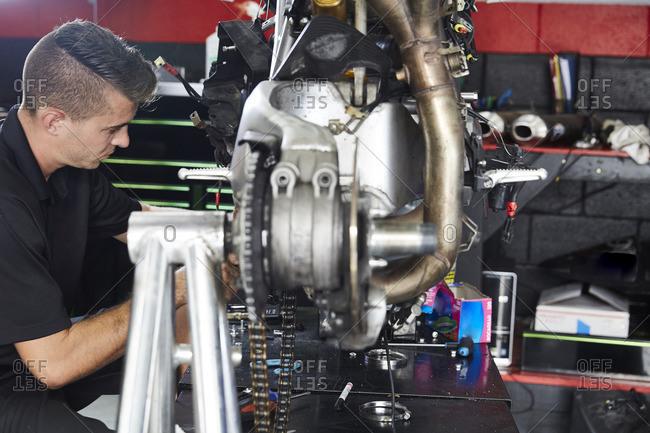 Side view of worker working on motorbike in factory