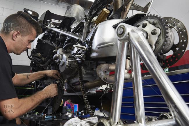 Worker examining motorcycle in factory