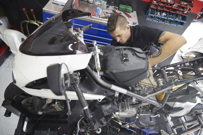High angle view of worker repairing motorcycle in workshop
