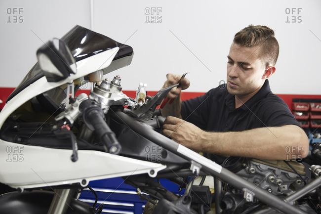 Worker repairing motorcycle in workshop