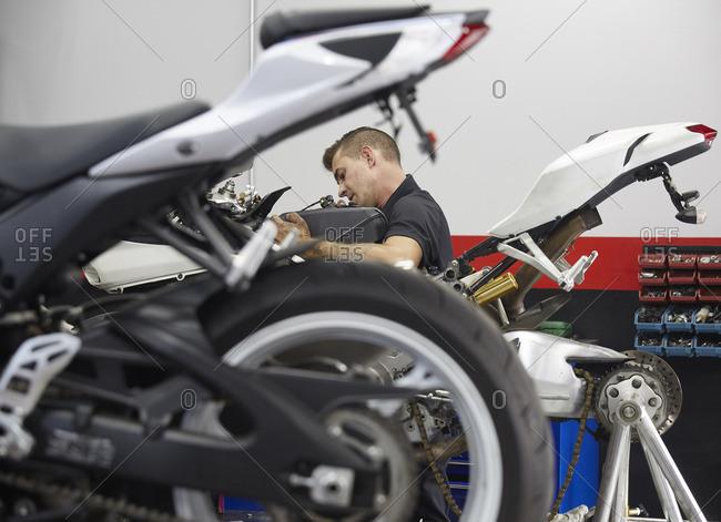 Side view of worker repairing motorbike in workshop