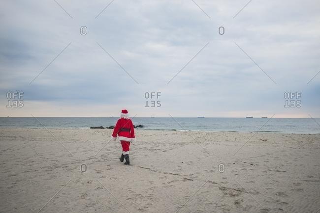 Rear view of senior man in Santa costume walking at beach