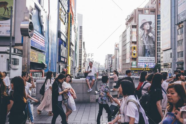 People on bridge against buildings in city