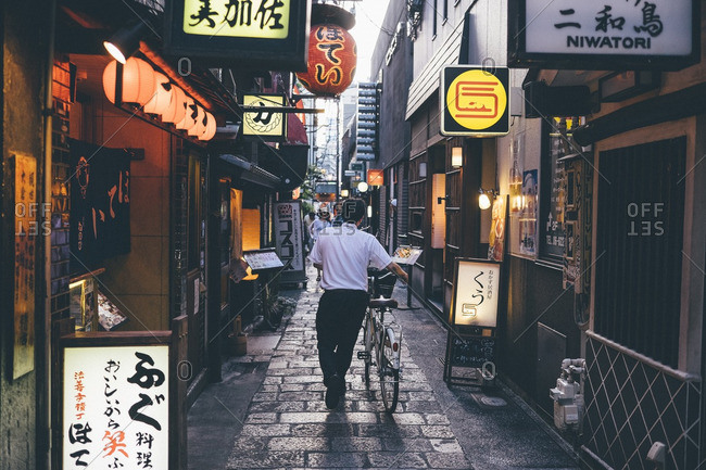 Osaka, Japan - July 10, 2016: Rear view of man with bicycle walking on paving stones amidst buildings