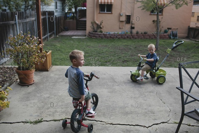 Brothers riding cycles in backyard