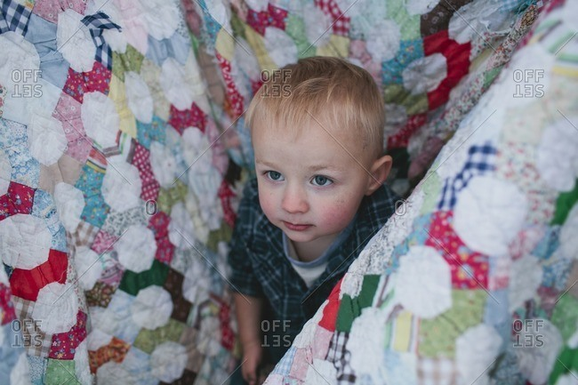 High angle view of cute boy amidst picnic blanket