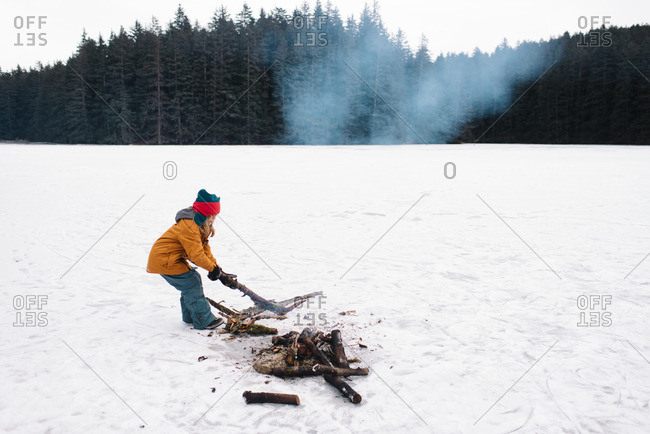 Child making fire in snowy field