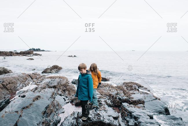 Boys walking rocky winter beach