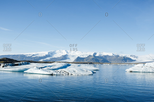 Iceland, Jökulsárlón lagoon. Tranquil landscape of glacier lagoon on a sunny day: calm crystal-clear lake with large chunks of ice sparkling in the sun and high mountains covered with snow in the background.