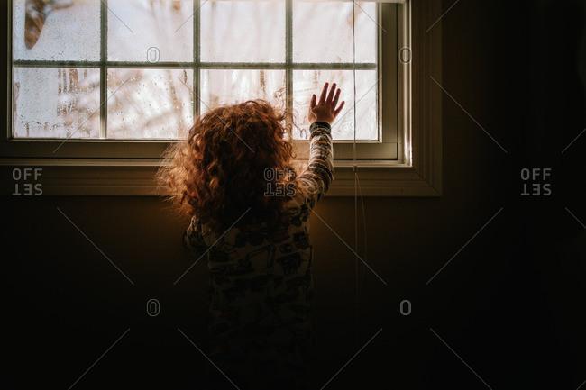 Child touching condensation on window