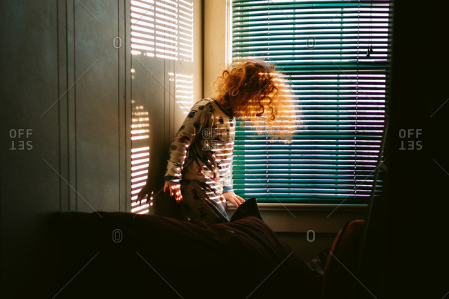Child in sunlight from window blinds