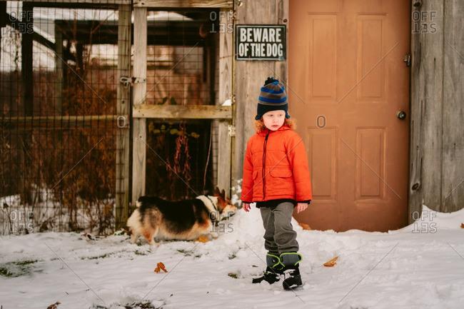Boy and dog in rural winter yard