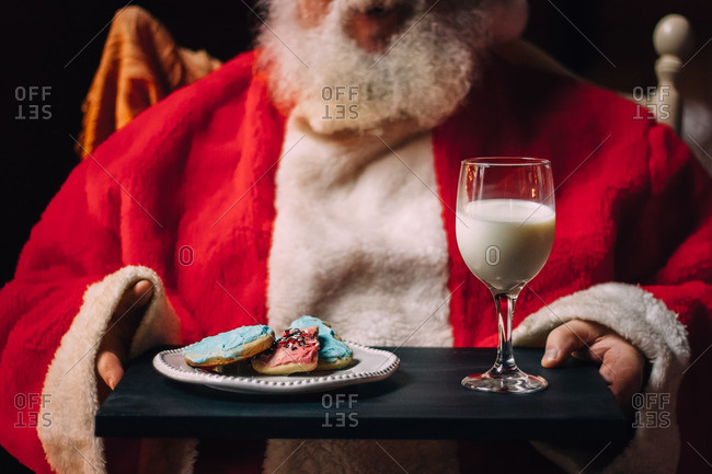 Santa Clause holding a tray of cookies