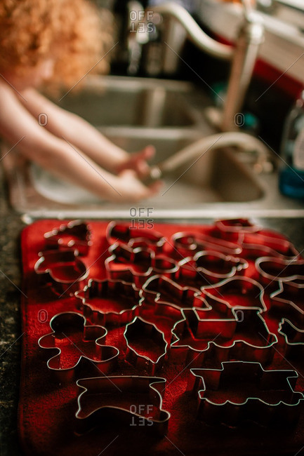 Child washing Christmas cookie cutters
