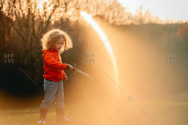 Child holding sword in sunlit yard