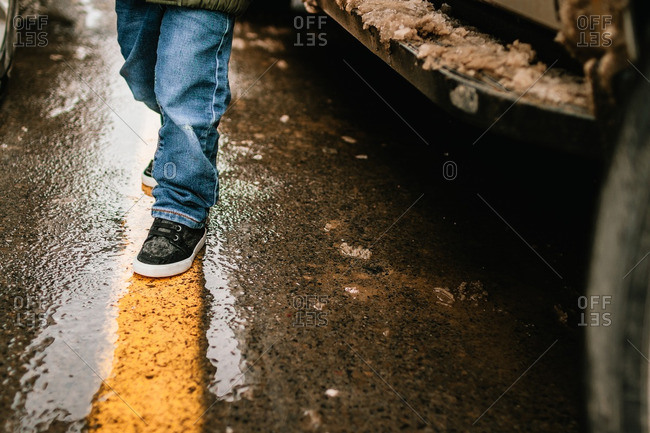 Child on yellow line in parking lot