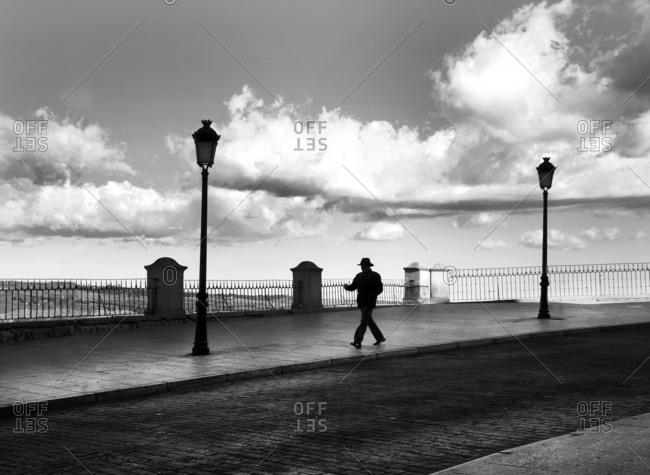 Toledo, Spain - January 17, 2017: Man silhouetted walking near lampposts