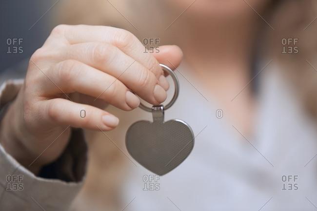 Woman holding heart shaped key ring