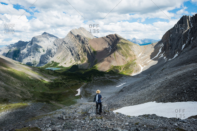 Man looks out over expansive mountains, lake, forest in summer