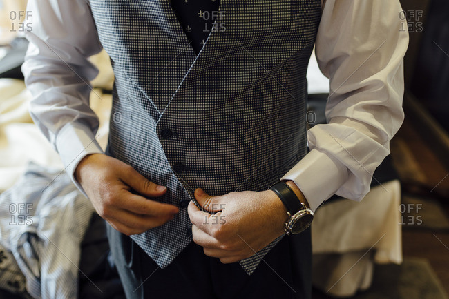 Groom buttoning his vest before a wedding