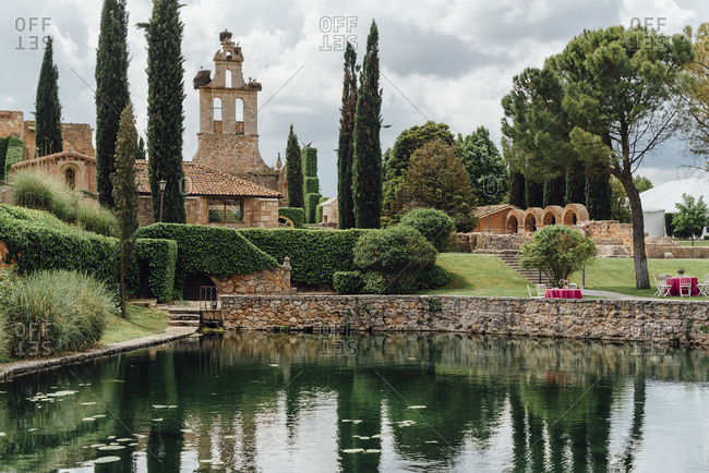 View of an ancient church surrounded by gardens and a lake