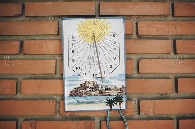 Vintage sundial hanging on a brick wall