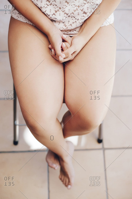 Detail of a woman with fingernail polish and legs crossed
