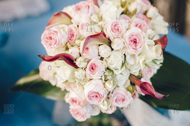 Bridal bouquet with white and pink roses over blue background