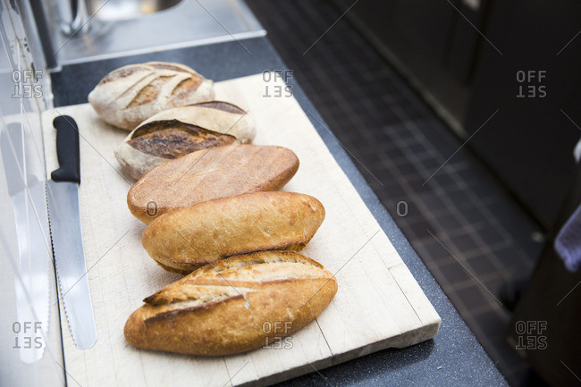 Different kinds of artisanal breads with a bread knife and cutting board in a restaurant kitchen in Amsterdam.