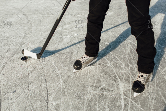 Cropped image of a man wearing ice skates holding a stick and a puck