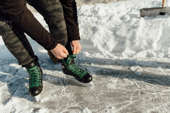 Cropped image of a man tying a green shoelace on his ice skates