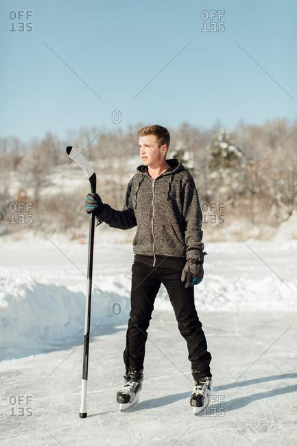 Man wearing ice skates holding a stick