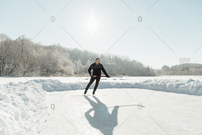Man in action playing ice hockey on a bright day