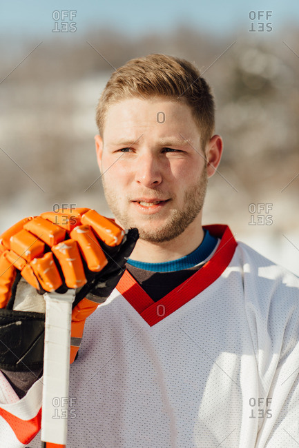 Portrait of a concerned hockey player with a glove and a stick