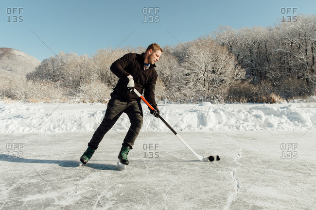 Man playing ice hockey on a frozen lake
