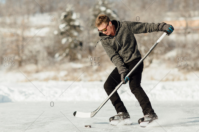 Man playing ice hockey on a frozen lake stopping and spraying ice
