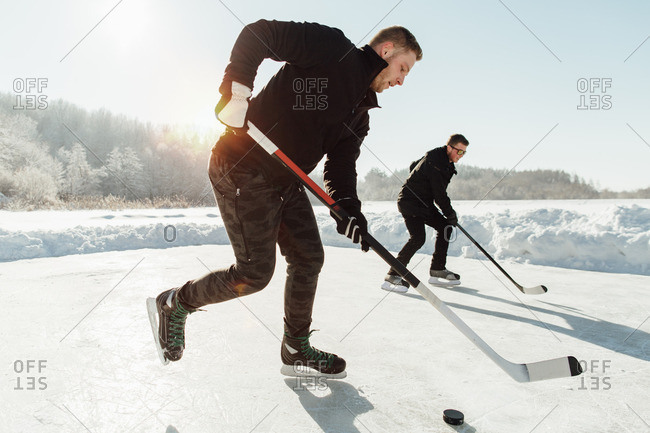 Side view of two men playing ice hockey on a frozen lake