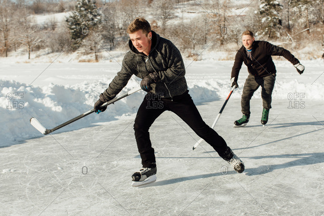 Two men playing ice hockey on a frozen lake
