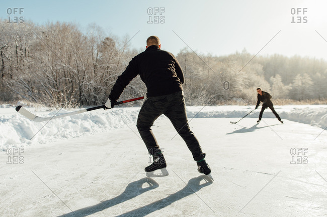 Rear view of two men playing ice hockey on a frozen lake