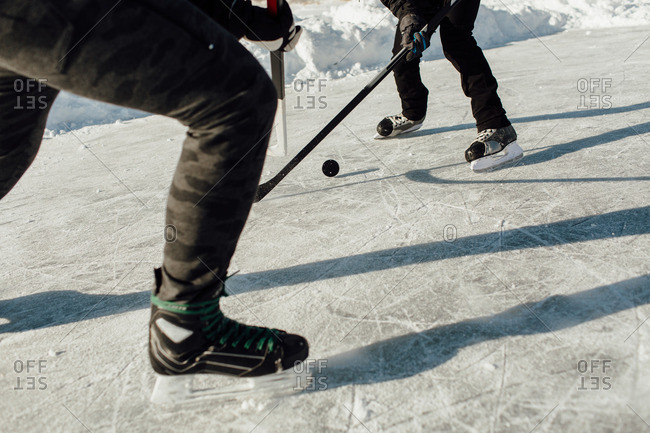 Cropped image of two men battling for a puck in face off