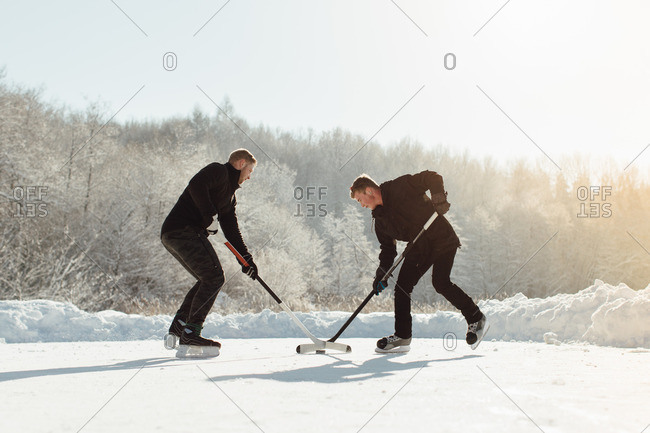 Two men battling for a puck on a frozen lake