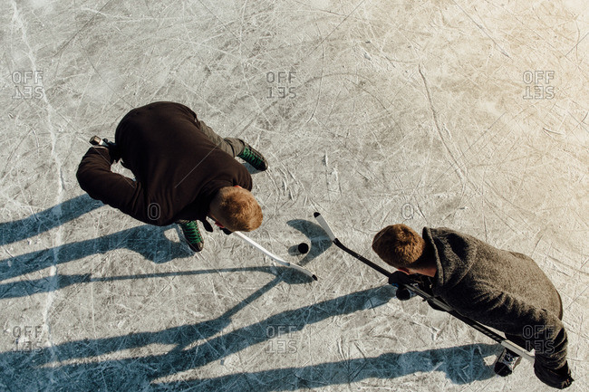 Overhead shot of two men battling for a puck in face off